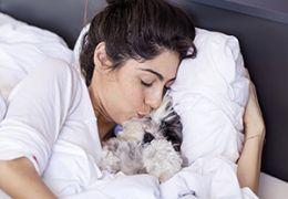 Femme câlins avec un chien dans le lit