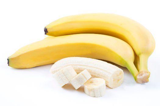 2 bananes entières et une pelées et coupées en dés sur bg blanc